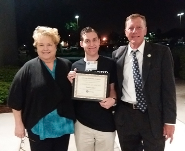 Andre Klass receives certificate from Jeff Triplett and Patty Mahany